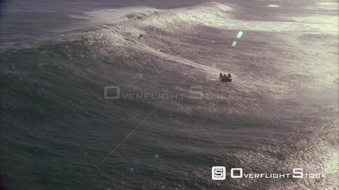 Aerial slow motion shot of a dingy and surfer riding the waves. Eastern Cape South Africa