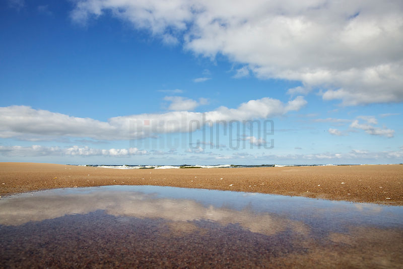 Clouds Reflected in a Puddle at the Beach