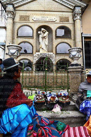 Aymara woman sitting with skulls in front of mausoleum in cemetery, Ñatitas festival, La Paz, Bolivia