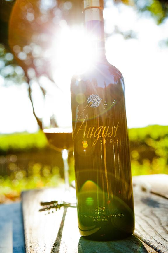 Strong backlighting behind a bottle and full glass of red wine being served outdoors on a warm sunny day