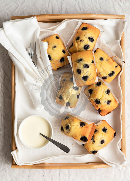 Individual blueberry loaf cakes with a bowl of cream on a wooden tray.