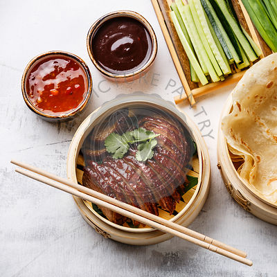 Sliced Peking Duck in bamboo steamer served with fresh cucumber, green onions, cilantro and roasted wheaten chinese pancakes ...