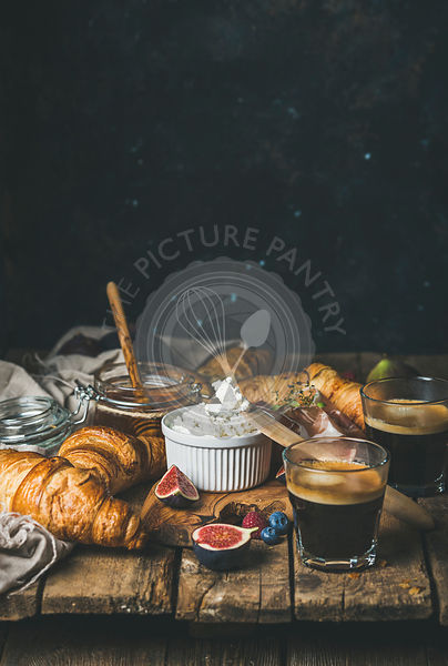 Breakfast with croissants, ricotta cheese, figs, fresh berries, prosciutto meat, honey and espresso coffee on rustic wooden t...