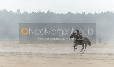 A boy gallops his pony on a beach