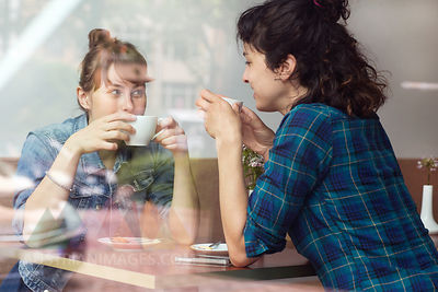 Two women sitting behind windowpane of a coffee shop drinking coffee