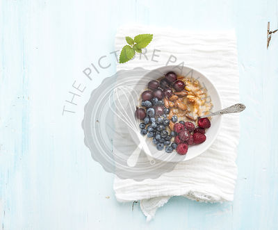 Healthy breakfast set. Bowl of oat porridge with fresh berries, almond and honey over white napkin. Top view, light blue back...