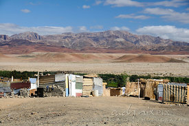 Shacks made of corrugated tin and reeds next to the thin band of vegetation that lines a river in the desert.