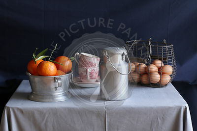 Still life with clementines,aluminum milk can,eggs and vintage coffee cups