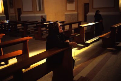 An elderly woman kneels and prays in a Catholic Church, Tirana, Albania. Religion was banned under the Communist regime