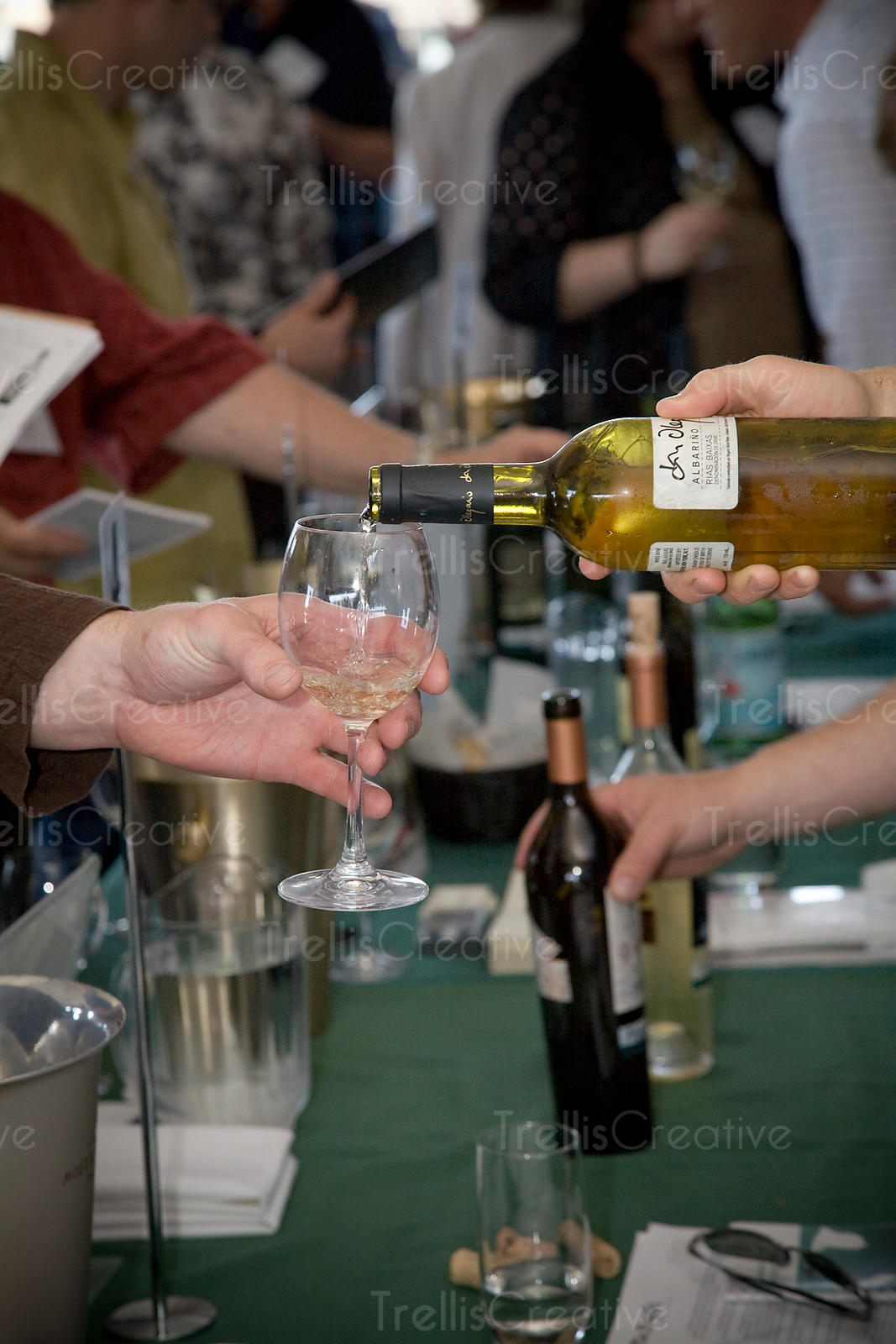 Pouring a glass of white wine at a tasting