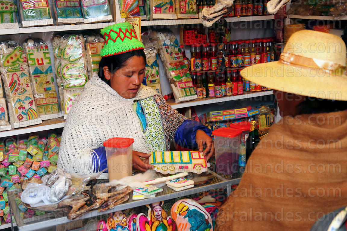 Woman selling items for offerings for Pachamama to customer inside her shop in Witches Market, El Alto, Bolivia