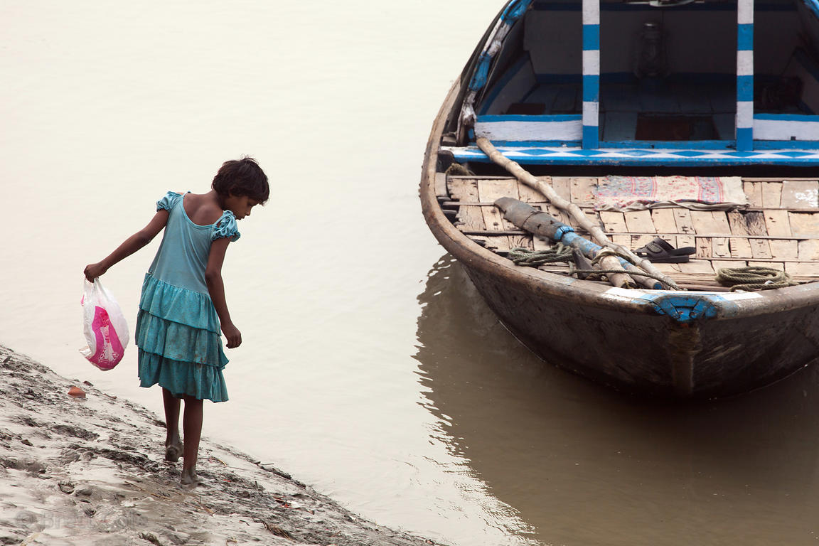 A girl scours the banks of the Hooghly River for... something.... near Princept Ghat, Kolkata, India.