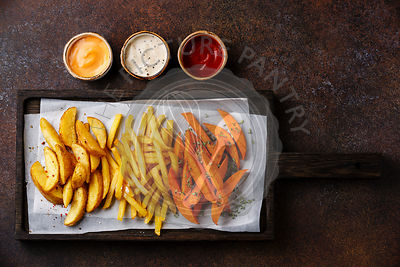 Variety of potatoes for garnish: potato wedges, french fries, sweet potato with three popular sauce for choice on brown backg...