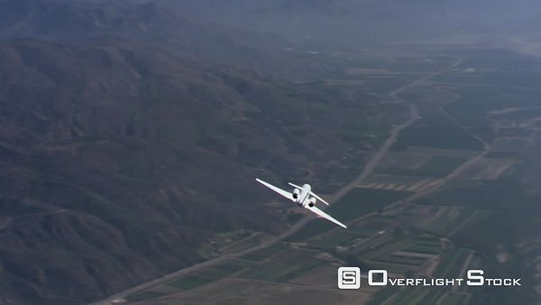 Air-to-air view of executive jet flying over valley