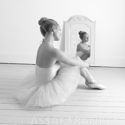 Young Ballerina sitting on floor in front of a mirror