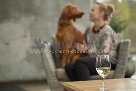 Blonde woman talking to Irish Setter mix sitting on outdoor chair with white wine glass on table