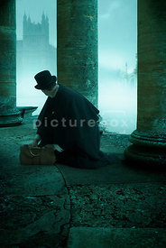 An atmospheric image of a Victorian man in a cloak and hat, crouching and taking something from a bag, in London, England.