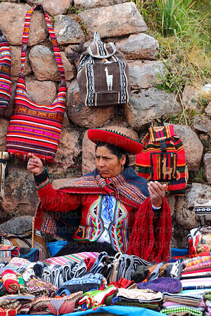 Quechua woman wearing traditional dress selling handicrafts in front of Inca wall at Chinchero market, Sacred Valley, Cusco R...