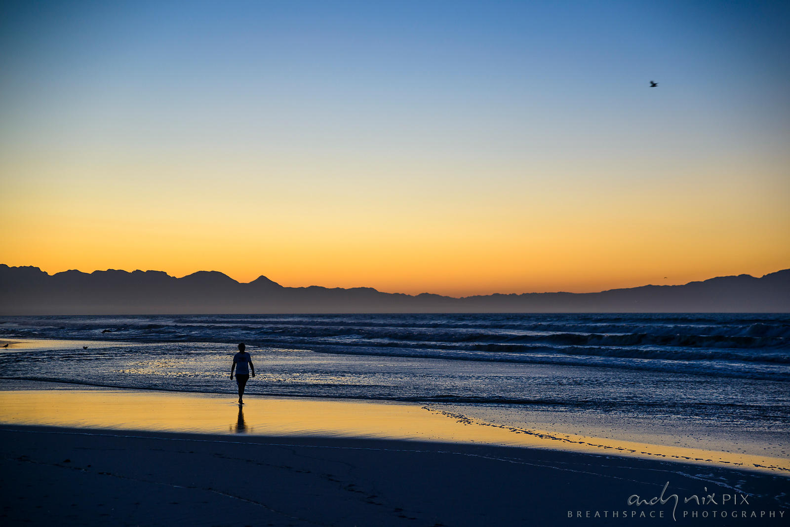 One silhouetted person  walking on the beach at dawn
