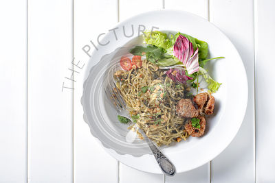 Top view of spaghetti with pesto sauce on white wooden table