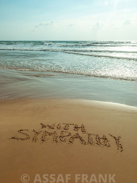 With Sympathy written in sand on the beach