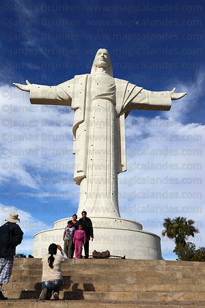 Bolivian family have their photo taken in front of Cristo de la Concordia statue, Cochabamba, Bolivia