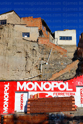 Monopol hardware store and bricks beneath slapdash building construction on unstable hillside, La Paz, Bolivia