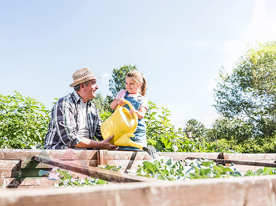 Grandfather and granddaughter in the garden watering plants