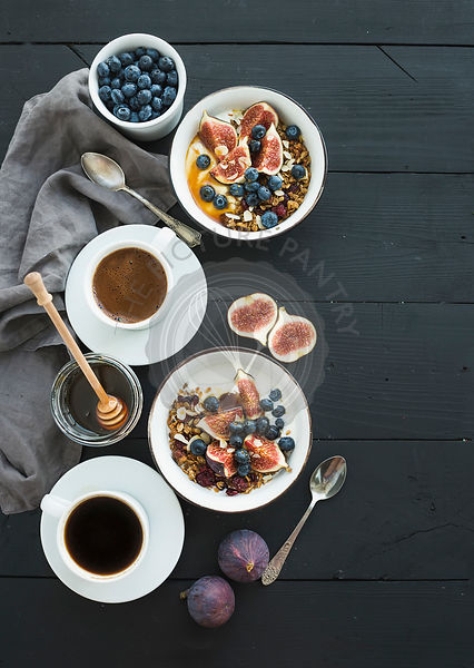 Healthy breakfast set. Bowls of oat granola with yogurt, fresh blueberries and figs, coffee, honey, over black wooden backdrop