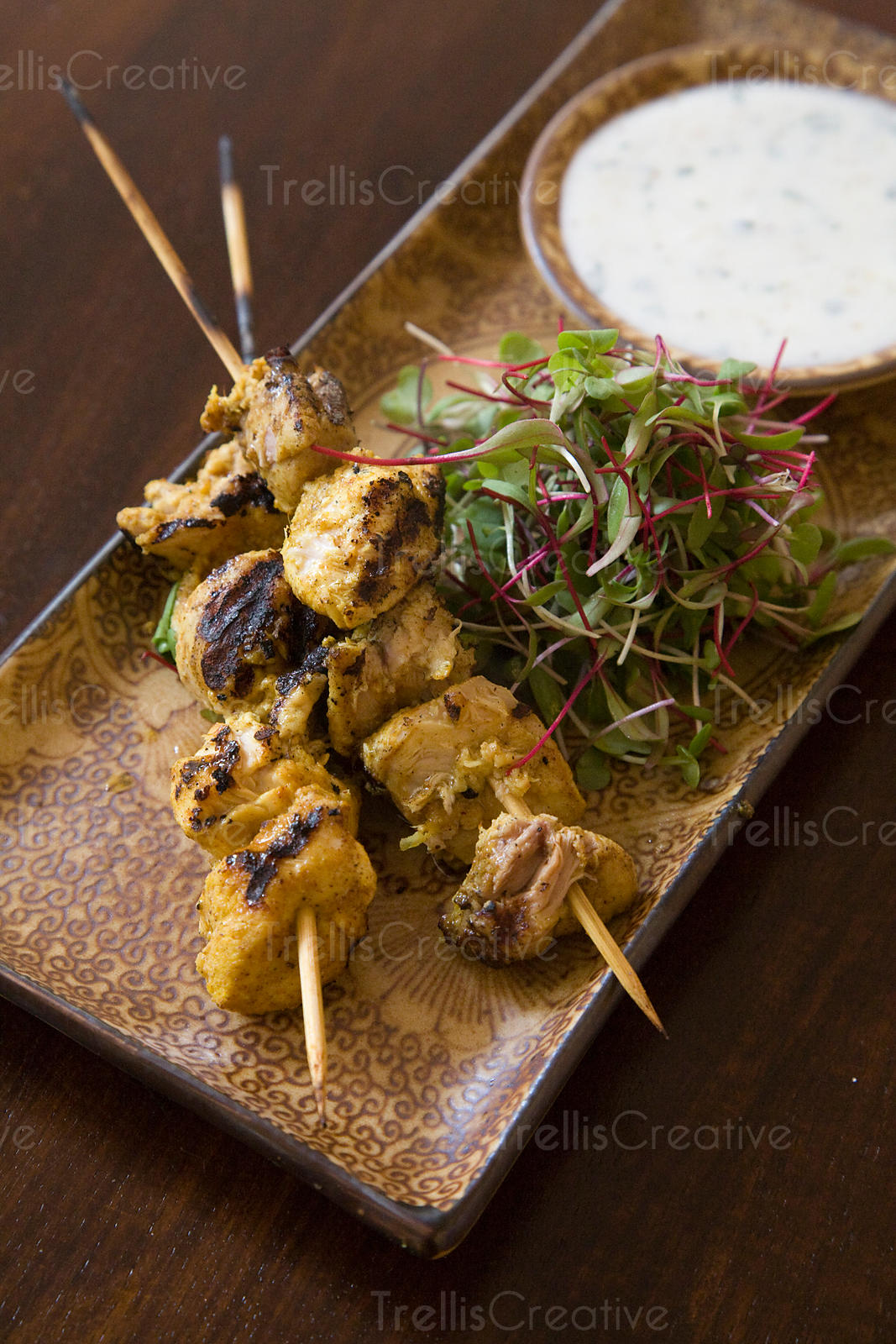 Skewered grilled chicken and yogurt sauce with baby greens