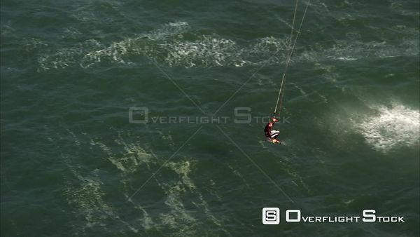Aerial shot of a kite surfer riding on the seas, gets lifted up then splashes back down. Eastern Cape South Africa