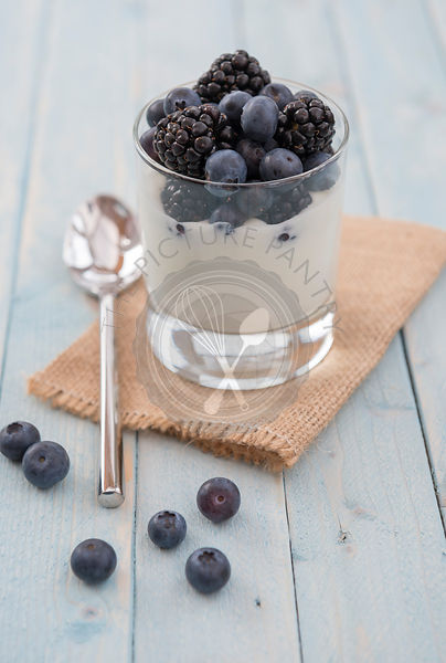 Blueberries and blackberries in natural yoghurt dessert or snack. Presented in a glass tumbler.