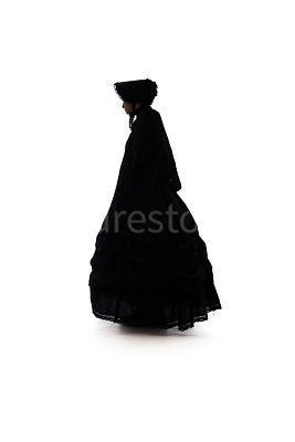 A Victorian woman, in a cape and bonnet, in silhouette – shot from low level.