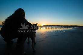 Silhouette of lady with arm around dog watching sunset on beach