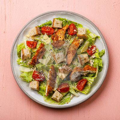 Caesar salad with Chicken breast meat on pink background