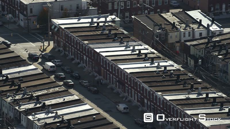 Close orbit over multiple row houses to reveal traffic on streets in Baltimore, Maryland. Shot in November
