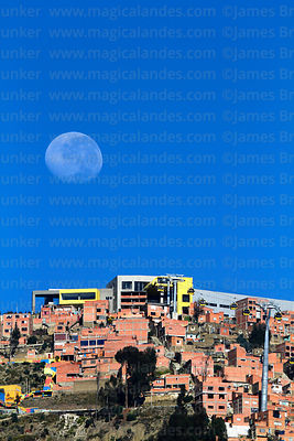 Nearly full waning moon setting behind Yellow Line cable car terminal in Ciudad Satelite (El Alto) and houses on hillside, se...