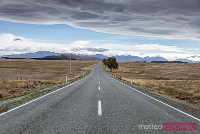 Road through desolate landscape in bad weather, New Zealand