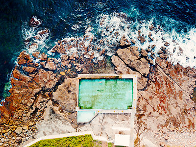 Coalcliff ocean pool is built into its seemingly crumbling rock shelf.  A lone swimmer doing laps of the pool Australia