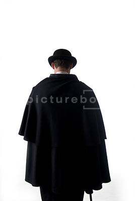 An image of a Victorian man in a cloak and hat from behind.