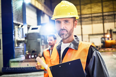 Portrait of confident man wearing protective workwear in factory