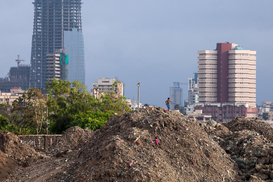 Children play barefoot on a mound of garbage in Mahim Bay, Mumbai, India.