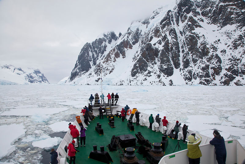 Tourists lining the deck ship Ushuaia in the Lemaire Channel clogged with sea ice, Antarctica.