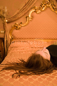 An atmospheric image of a woman slumped or sleeping on a bed.
