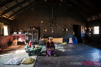 Old asian woman sitting inside her house, Shan state, Myanmar