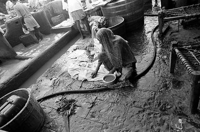 A woman scrubs clothes at the Dhobi Ghat