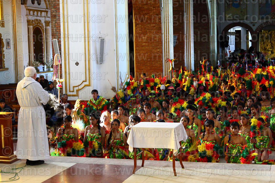 Priest blessing a tobas dance group inside Sanctuary of Virgen del Socavón, Oruro Carnival, Bolivia