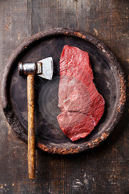 Raw fresh meat and meat cleaver on dark background