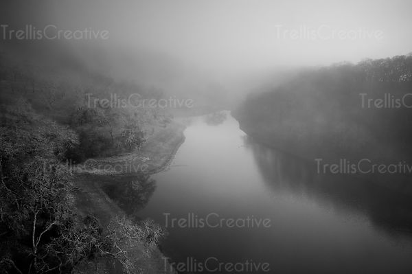 Aerial view of a tranquil river with the mist lifting to reveal the landscape of bare trees
