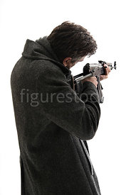 A semi-silhoeuette of a mystery man in a big coat, pointing an AK-47 – shot from eye level.